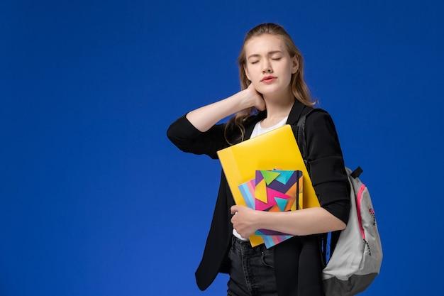 Вид спереди студентка в черной куртке с рюкзаком, держащая файлы с тетрадями с шейкой на синей стене, урок университета колледжа