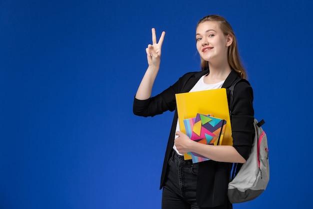 青い壁の大学のレッスンでコピーブックとファイルを保持しているバックパックを身に着けている黒いジャケットの正面図の女子学生