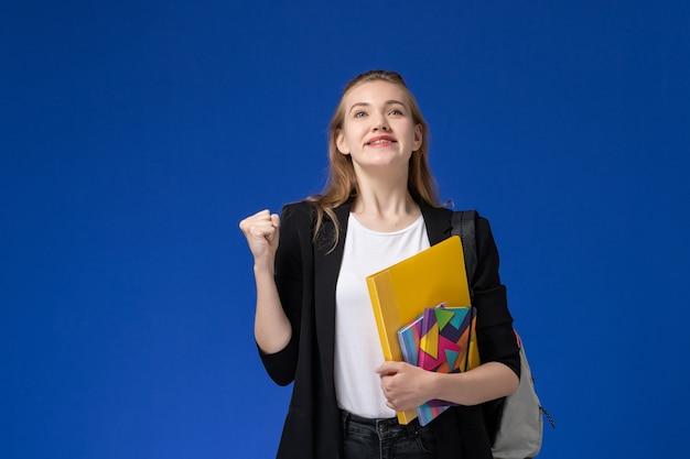 青い壁の大学のレッスンで喜んでコピーブックとファイルを保持しているバックパックを身に着けている黒いジャケットの正面図の女子学生