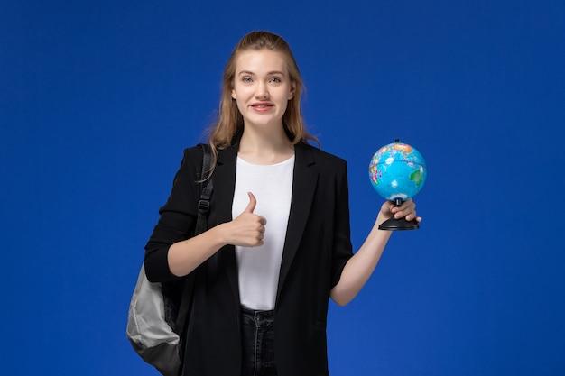 青い壁の学校の大学の地球に小さな地球を保持しているバックパックを身に着けている黒いジャケットの正面図女子学生
