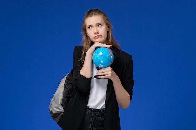 青い壁の学校の大学のレッスンで小さな地球を保持しているバックパックを身に着けている黒いジャケットの正面図の女子学生