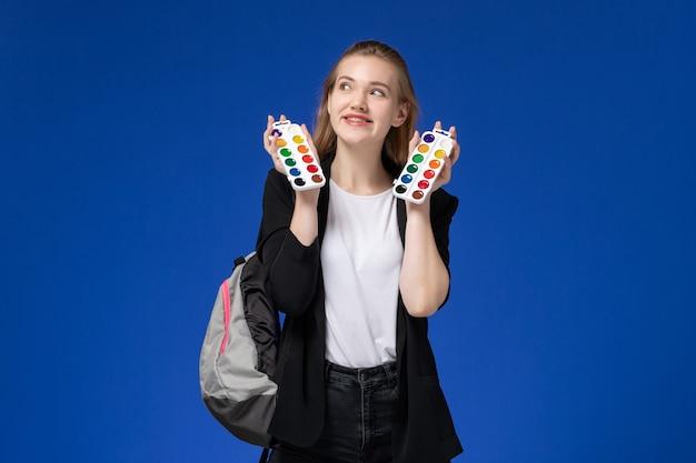 파란색 벽 그림 예술 학교 대학 대학에 그리기위한 페인트를 들고 배낭을 입고 검은 재킷에 전면보기 여자 학생