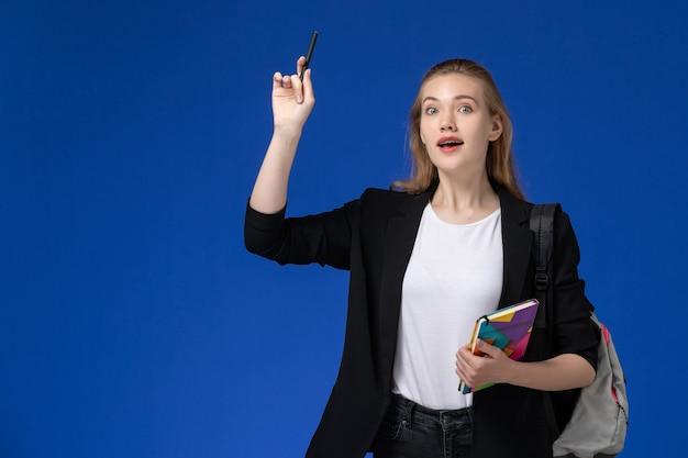 Вид спереди студентка в черной куртке в рюкзаке, держащая ручку и тетрадь на синей стене, уроки колледжа и университета