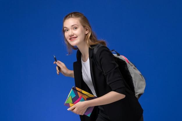 青い壁の本の学校の大学のレッスンで笑っているペンとコピーブックを保持しているバックパックを身に着けている黒いジャケットの正面図女子学生