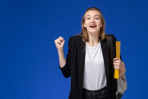 黄色のファイルを保持し、青い壁の学校の大学で喜んでいるバックパックを身に着けている黒いジャケットの正面図女子学生