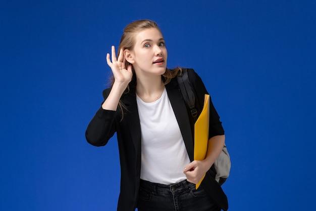 Вид спереди студентка в черной куртке в рюкзаке с желтыми папками на синей стене урок школы колледжа университета