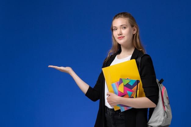 青い壁の大学のレッスンでコピーブックとファイルを保持しているバックパックを身に着けている白いシャツと黒いジャケットの正面図の女子学生