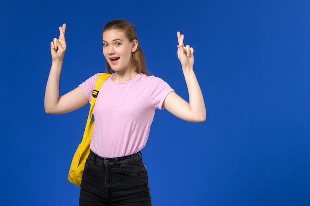 Front view of female student in pink t-shirt with yellow backpack crossing her fingers on blue wall