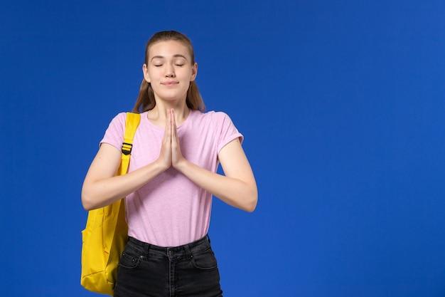 Vista frontale della studentessa in maglietta rosa con zaino giallo solo in piedi e in posa sulla parete blu