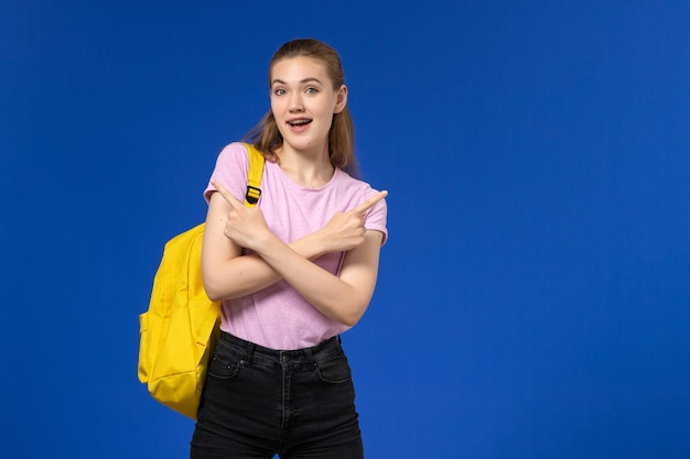 Front view of female student in pink t-shirt with yellow backpack posing on blue wall