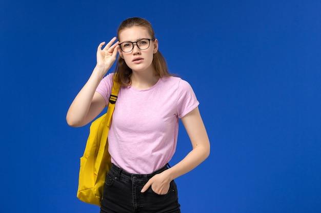 Vista frontale della studentessa in maglietta rosa con zaino giallo in posa sulla parete blu