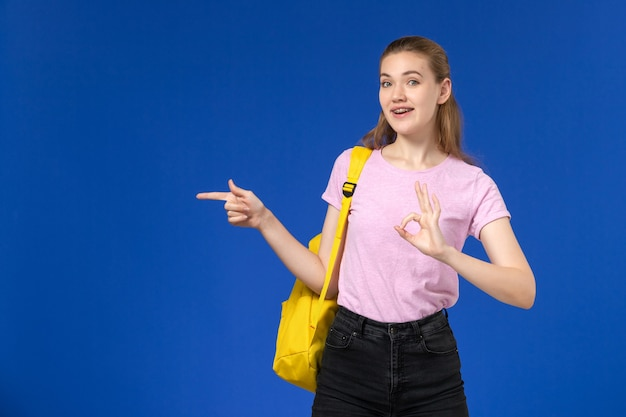 Front view of female student in pink t-shirt with yellow backpack posing on the light-blue wall