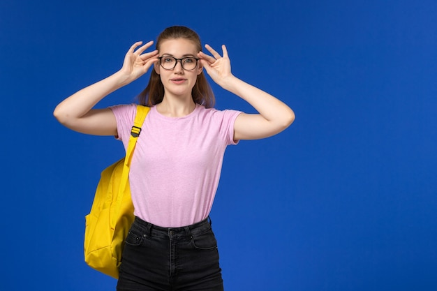 Front view of female student in pink t-shirt with yellow backpack wearing optical sunglasses on blue wall