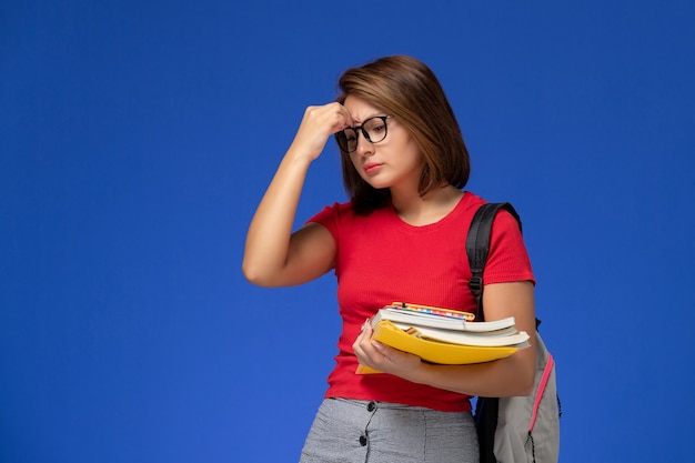 Front view of female student in red shirt with backpack holding books and files depressed on blue wall