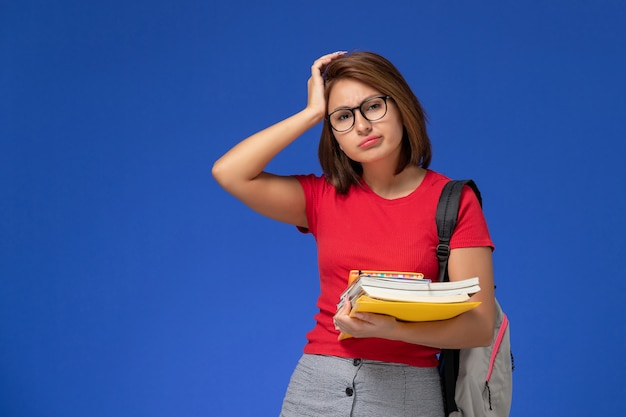 Front view of female student in red shirt with backpack holding books and files depressed on light-blue wall