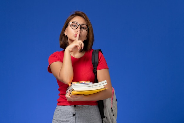 Vista frontale della studentessa in camicia rossa con zaino in possesso di libri e file sulla parete azzurra