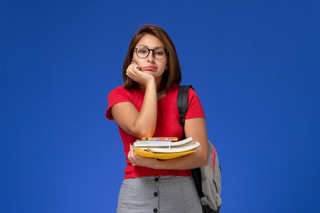 Front view of female student in red shirt with backpack holding books and files on the light blue wall