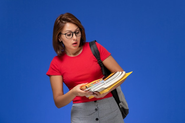 Front view of female student in red shirt with backpack holding books and files on the lightblue wall