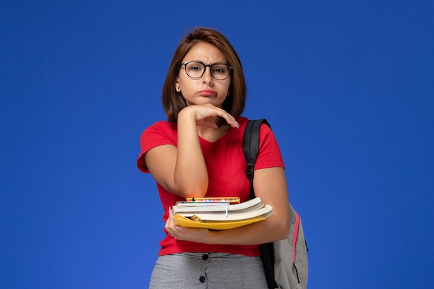 Front view of female student in red shirt with backpack holding books and files thinking on blue wall