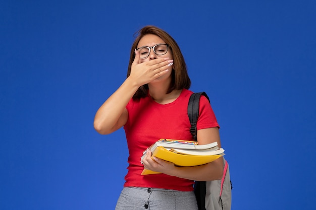 Front view of female student in red shirt with backpack holding books and files yawning on blue wall