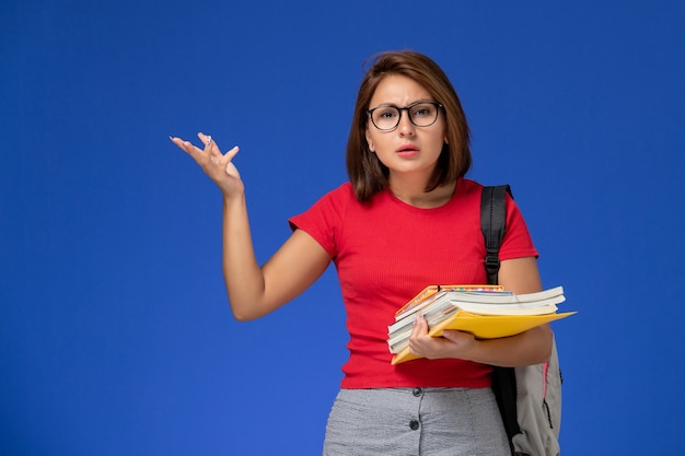 Front view of female student in red shirt with backpack holding books and files