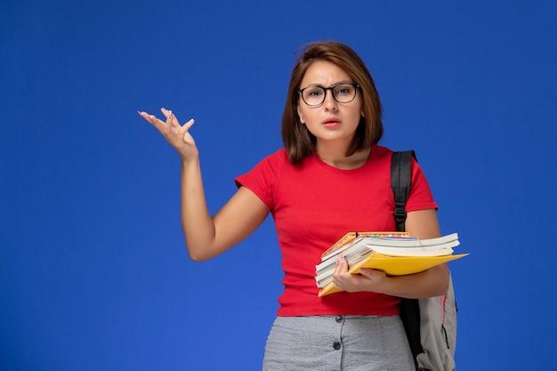Vista frontale della studentessa in camicia rossa con zaino in possesso di libri e file