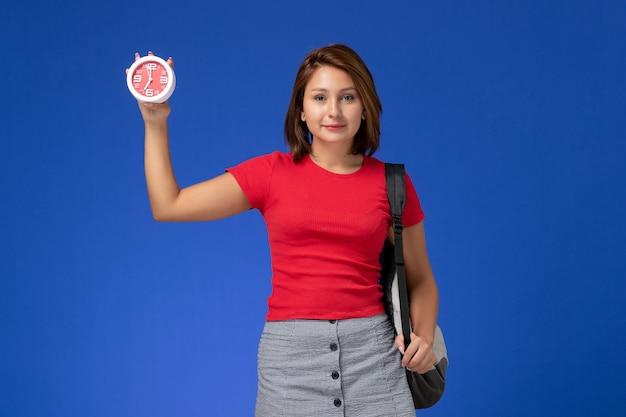 Vista frontale della studentessa in camicia rossa con lo zaino che tiene gli orologi sulla parete blu