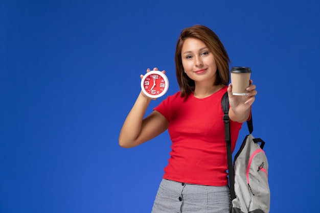 Vista frontale della studentessa in camicia rossa con lo zaino che tiene gli orologi e il caffè sulla parete blu