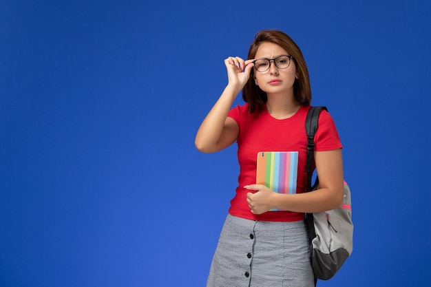 Front view of female student in red shirt with backpack holding copybook on the blue wall