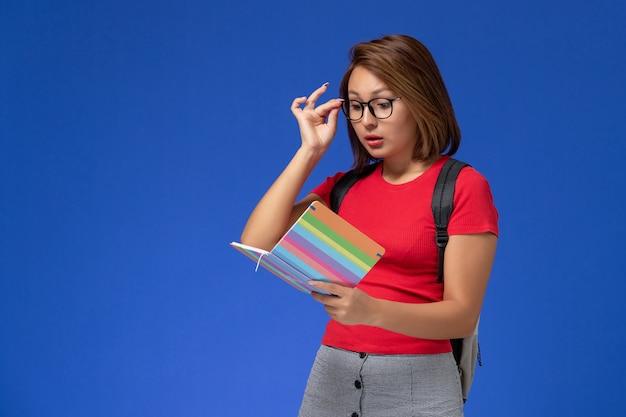 Vista frontale della studentessa in camicia rossa con lo zaino che tiene la lettura del quaderno sulla parete blu