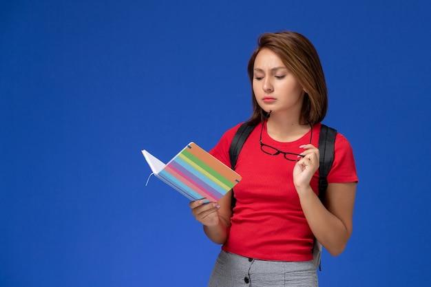 Vista frontale della studentessa in camicia rossa con zaino che tiene il quaderno e leggerlo sulla parete blu