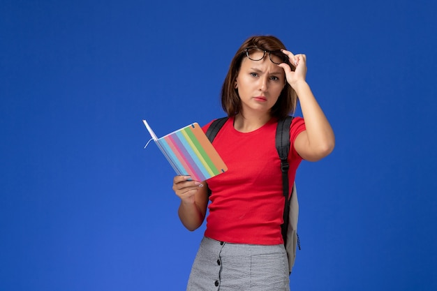 Vista frontale della studentessa in camicia rossa con lo zaino che tiene il quaderno che toglie gli occhiali da sole sulla parete blu