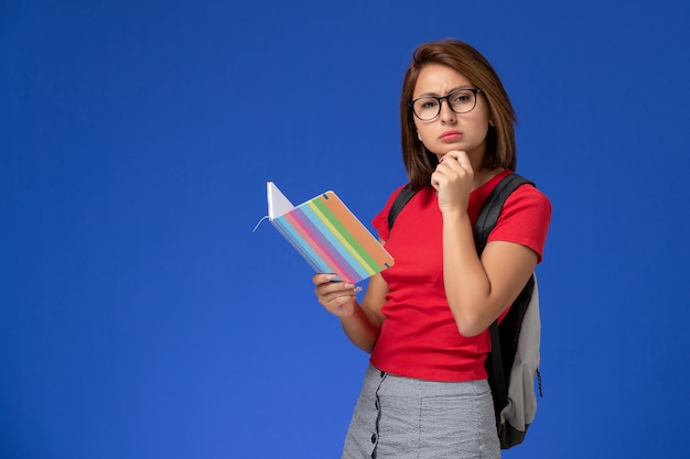 Front view of female student in red shirt with backpack holding copybook thinking on blue wall