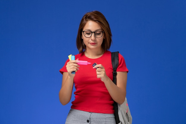 Front view of female student in red shirt with backpack holding felt pens on blue wall