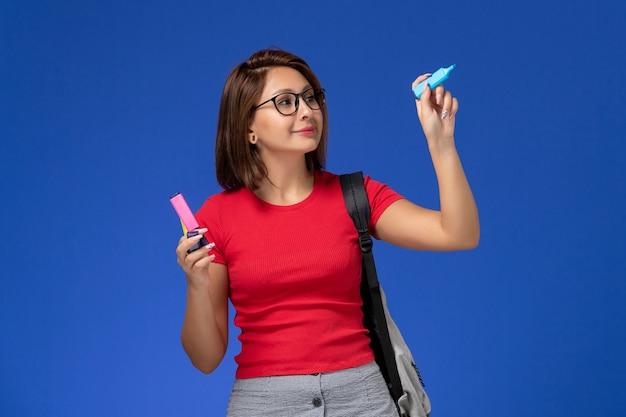 Vista frontale della studentessa in camicia rossa con lo zaino che tiene i pennarelli sulla parete blu