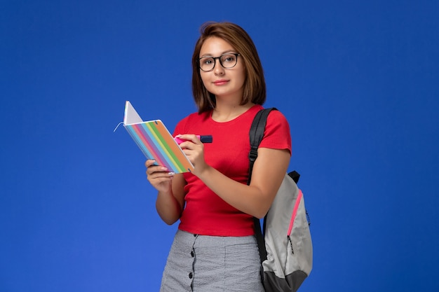 Front view of female student in red shirt with backpack holding felt pens and copybook on blue wall