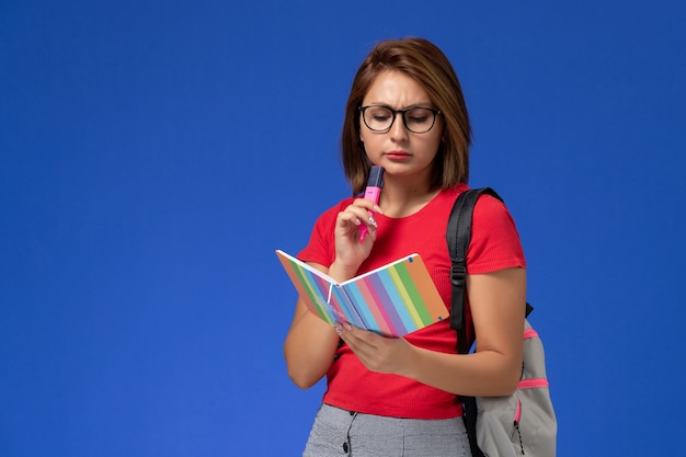 Front view of female student in red shirt with backpack holding felt pens reading copybook on blue wall