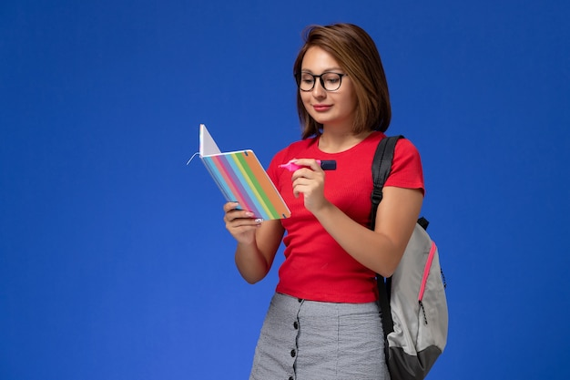 Front view of female student in red shirt with backpack holding felt pens reading copybook on the blue wall