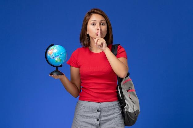 Vista frontale della studentessa in camicia rossa con zaino che tiene piccolo globo sulla parete blu