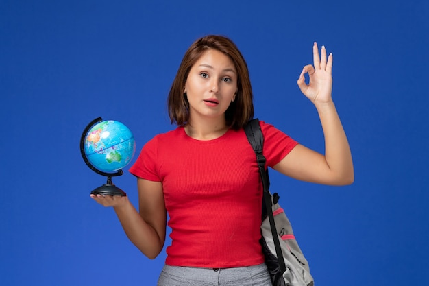 Front view of female student in red shirt with backpack holding little globe on blue wall