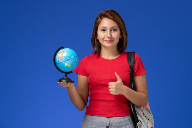 Front view of female student in red shirt with backpack holding little globe smiling on blue wall