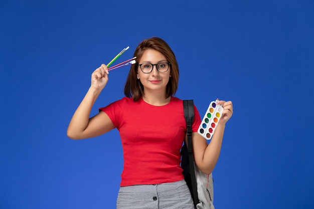 Front view of female student in red shirt with backpack holding paints for drawing and brushes on blue wall
