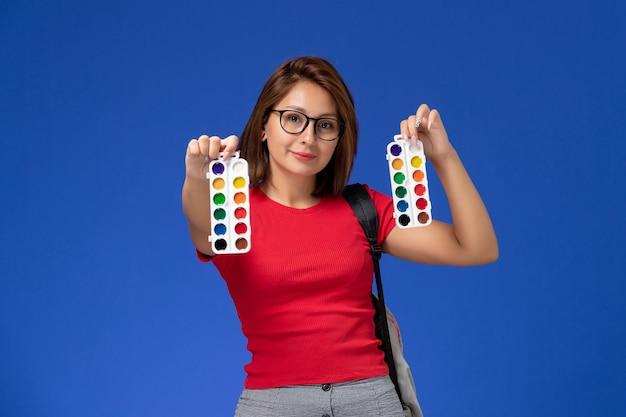 Vista frontale della studentessa in camicia rossa con lo zaino che tiene le vernici per disegnare sorridente sulla parete blu