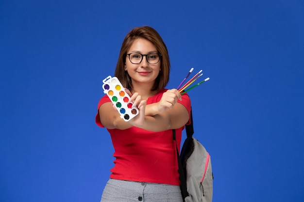 Front view of female student in red shirt with backpack holding paints for drawing and tassels on blue wall