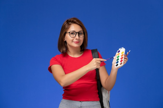 Front view of female student in red shirt with backpack holding paints for drawing and tassels smiling on the blue wall