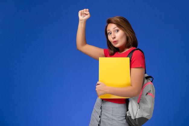 Vista frontale della studentessa in camicia rossa con lo zaino che tiene file gialli sulla parete azzurra