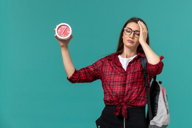 Vista frontale della studentessa che indossa uno zaino che tiene gli orologi sulla parete blu