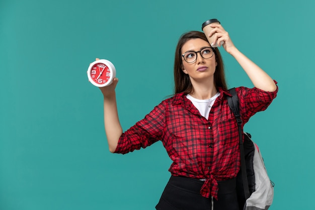 Vista frontale della studentessa che indossa uno zaino con orologi e caffè sulla parete blu
