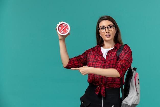 Vista frontale della studentessa che indossa uno zaino in possesso di orologi sulla parete blu chiaro