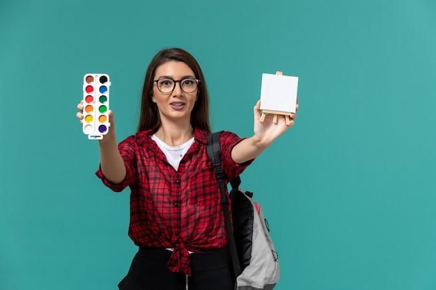 Vista frontale della studentessa che indossa uno zaino in possesso di cavalletto e vernici sulla parete azzurra